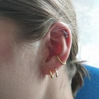 Nordik Piercing: Studio de piercing dans le 76: piercing helix avec bijou 3 cristaux et piercing conch avec anneau doré torsadé